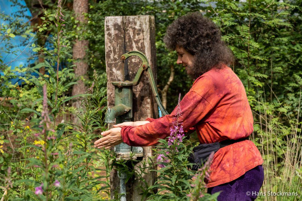 Marieke in haar bloementuin, aan de oude pomp.