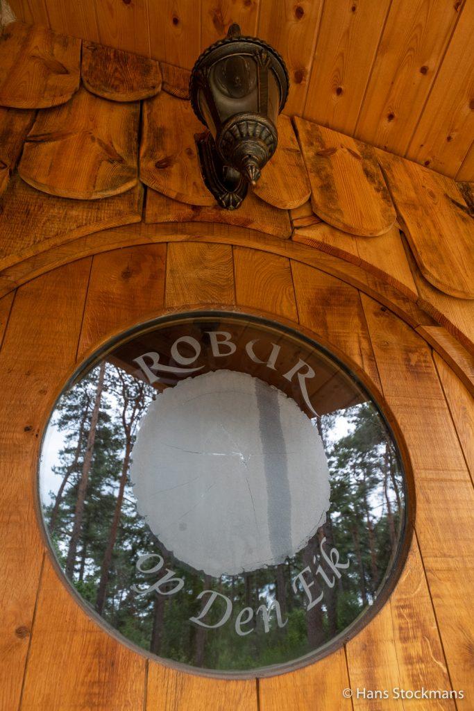 Weerspiegeling van dennen in het venster van Roburs voordeur.